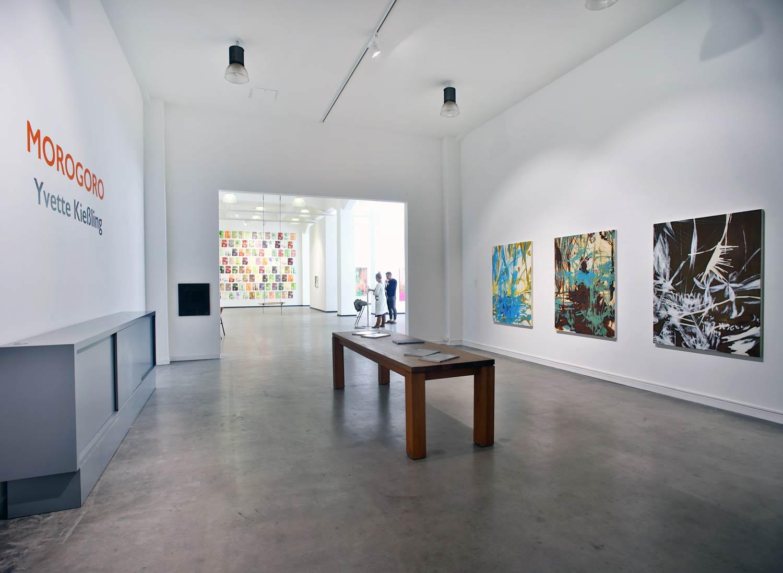 Eingangsbereich der Barlach-Halle K, eine Ausstellung-Halle in Hamburg. An der Wand links ist in großen, organgenen Lettern Morogoro sowie der Name der Künstlerin Yvette Kießling zu lesen. An der Wand rechts sind drei großformatige Ölbilder, in Blau-, Pastell- und Brauntönen, mit tropischen Motiven zu sehen. In der Mitte des Bildes steht ein großer brauner Holztisch mit Ausstellungskatalogen. Der Raum öffnet sich im Bildhintergrund. Es sind zwei Besucher und weitere Bilder zu sehen